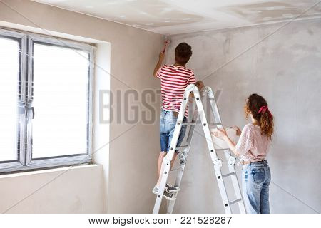 Beautiful young couple standing on ladder painting walls in their new house using paint brushes. Home makeover and renovation concept. Rear view.