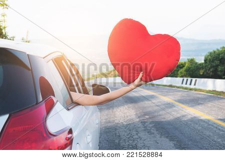 Relaxed happy traveler, Young beatiful asian gilr holding red heart and Reach out of the car at sunset and beautiful view with mountain road background.