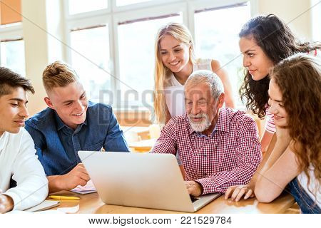 Group of high school student and their teacher with laptop studying.