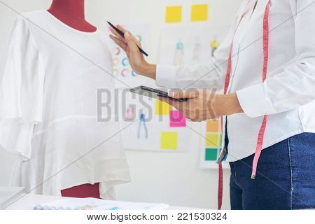 Stylish fashion designer working with measure red dummy as sketches in digital tablet of new collection in art, profession and job occupation, Creative Design and Artistic Concept.