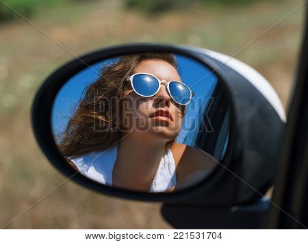 female face in sunglasses in the car side view mirror