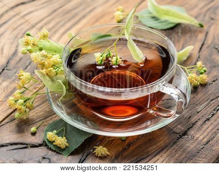 Cup of linden tea and lime flowers on the wooden table.