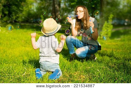 Mom and son let the soap bubbles on the lawn in the forest, on a bright, sunny day