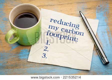 reducing my carbon footprint list - handwriting on a napkin with a cup of espresso coffee