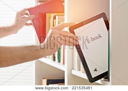 Man taking modern ebook reader from a bookshelf. Other hand in background with classic book.