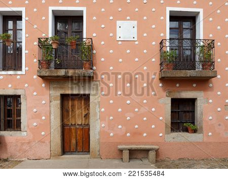 Orange Facade of old house with windows and wooden door. Cáceres, Spain.