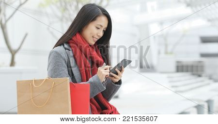 Shopping woman holding paper bag and use of mobile phone in city