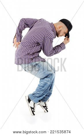 Young rapper in jeans and plaid shirt stands on tiptoe in profile, holds visor isolated on white background.