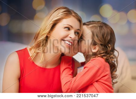 family and people concept - happy mother and daughter whispering something into ear over festive lights background
