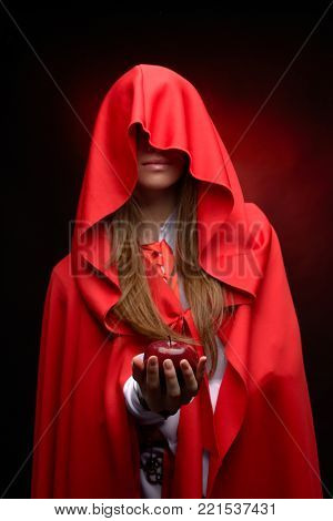 beautiful woman with res cloack holding red apple in studio