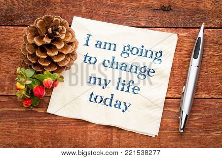 I am going to change my life today - inspiraitonal handwriting on a napkin against rustic wood