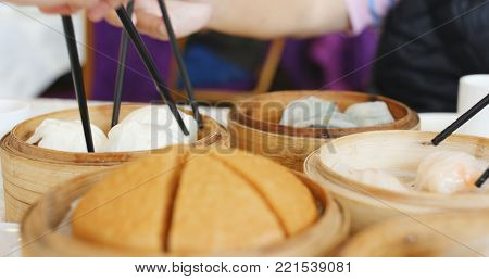 Family gathering in Chinese restaurant, Steamed dim sum basket on the table, people eating with chopstick