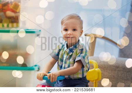 childhood, toys and people concept - happy little baby boy driving ride-on toy car at home