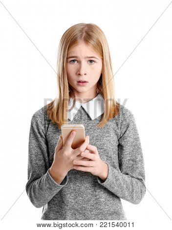 Sad teenage girl with smartphone on white background