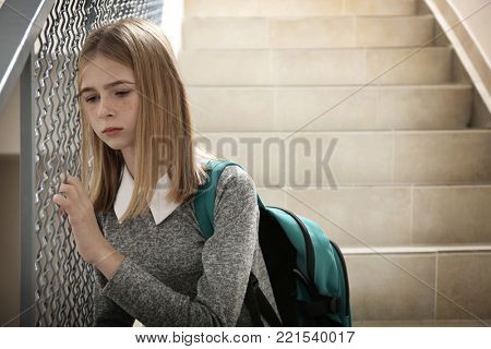 Upset teenage girl with backpack on stairs indoors