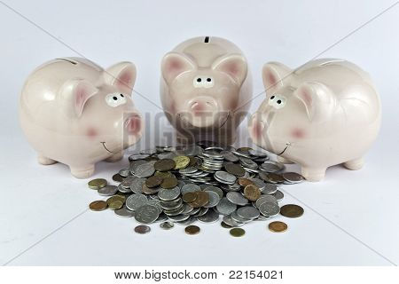 three pink piggy banks feasting on hip of coins