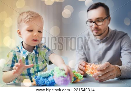 family, childhood, creativity, activity and people concept - happy father and little son playing with ball clay at home