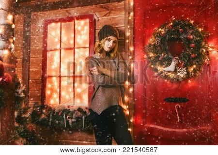 Beautiful young woman is standing on the porch of a house decorated for Christmas. Time for miracles. Merry Christmas and Happy New Year.