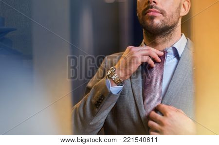 sale, shopping, fashion, style and people concept - close up of young man in suit choosing and trying tie on and looking to mirror in mall or clothing store