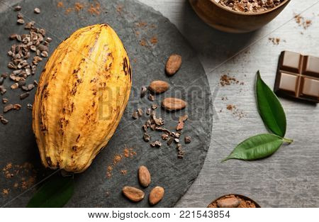 Slate plate with ripe yellow cocoa pod, beans and nibs on grey background