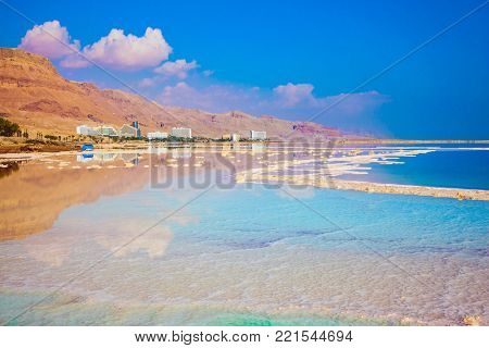 The Dead Sea, Israel. Hot summer day at the seaside resort. The evaporated salt has developed into fantastic patterns. The concept of medical and ecological tourism