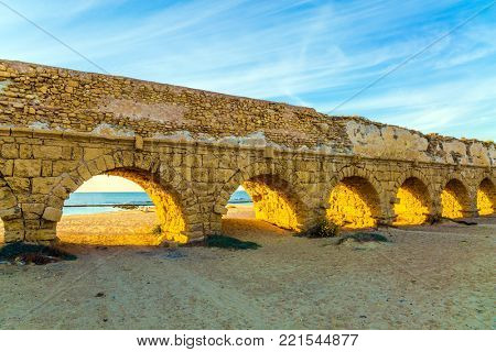 The aqueduct, built in the early Byzantine period. Fantastic sunset on the Mediterranean coast in Caesarea. The sandy beach is trampled by tourists. Concept of ecological and historical tourism