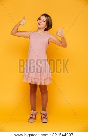 Portrait of happy carefree pretty girl in dress smiling and showing thumbs up isolated