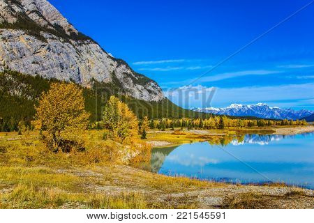 Concept of ecological and active tourism. Rocky Mountains are reflected in the smooth turquoise water of the Abraham lake