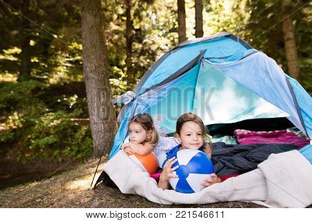 Two beautiful little girls with colorful beach balls sitting in tent, camping in the forest.