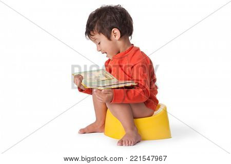 Toddler boy sitting on a potty and reading a book on white background