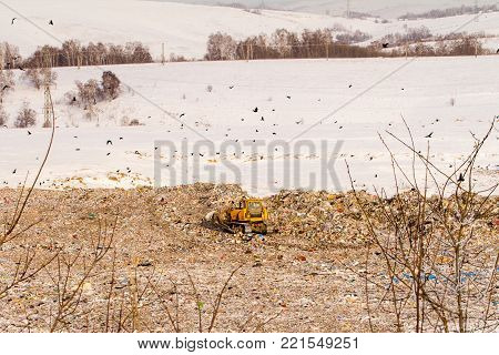 dump truck at the dump in winter in the snow