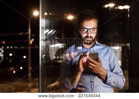 Thoughtful hipster businessman with smart phone in his office working late at night.