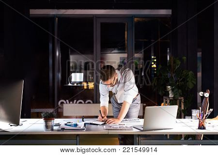 Thoughtful hipster businessman in his office working late at night at desk with computer and laptop.