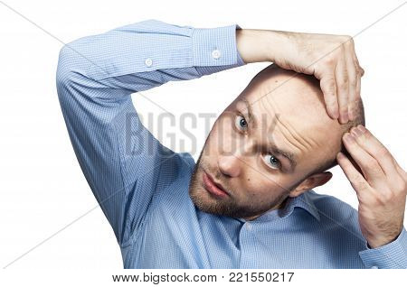White bald man in a blue shirt on a white background looks in the mirror his head