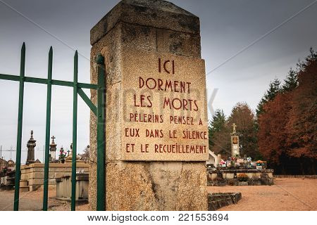ORADOUR SUR GLANE, FRANCE - December 03, 2017 : at the entrance of the cemetery a stone plaque where it is written - here sleep the dead pilgrims think of them in silence and meditation