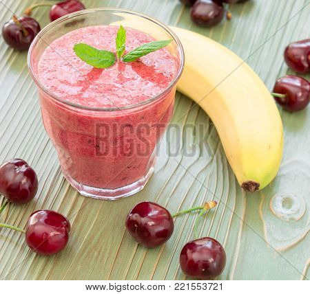 Glass of cherries and bananas smoothie nearby ingredients. Horizontal. Close-up.