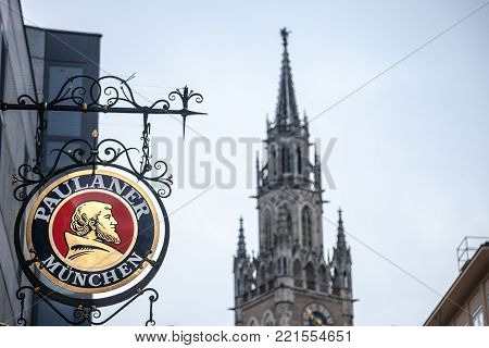 MUNICH, GERMANY - DECEMBER 17, 2017: Paulaner Beer logo in front of Munich New Town Hall (Neues Rathaus). Paulaner Bier is one of the symbols and main beers of Munich and Bavaria