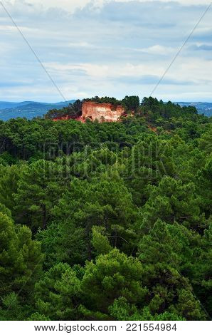 Beautiful landscape with red cliff and pine forest around village of Roussillon at twilifgt, Provence, France