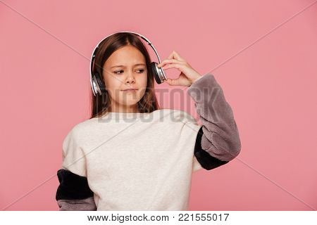Young displeased girl push her headphones because of loudness isolated over pink