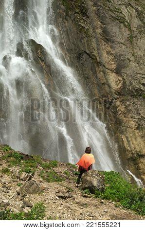 Woman in an orange stole sits near a waterfall.