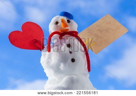Little happy christmas snowman in blue screw top as hat red scarf and with clip red heart love symbol valentine paper card text message outdoor. Winter season seasonal specific valentine's day. Blue sky background.
