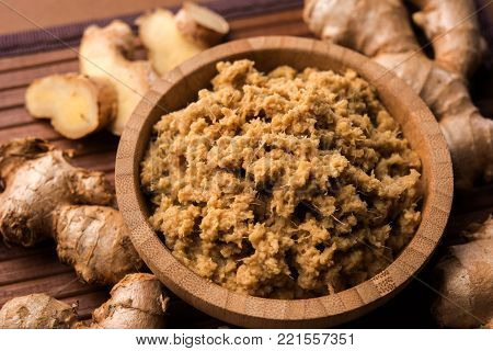 Fresh mashed Ginger / Ginger paste in white bowl with raw ginger over white background