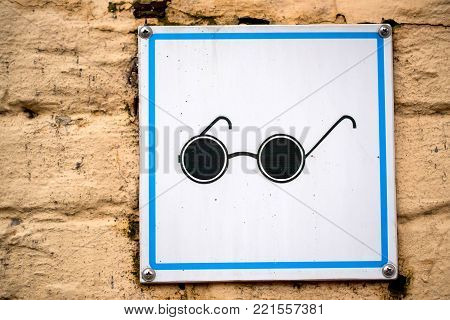 Close up sign with black glasses on it for people with visual impairment