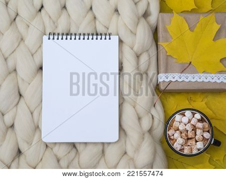 Cozy composition, notebook, hot chocolate with marshmallows, merino wool blanket, warm and comfortable atmosphere. Knit background. Flat lay. Top view. Copy space. Autumn concept.Wrapped gifts.
