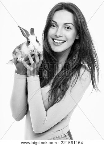 young woman or girl with pretty smiling face with long hair in pink shirt holding little rabbit fluffy domestic animal pet isolated on white background
