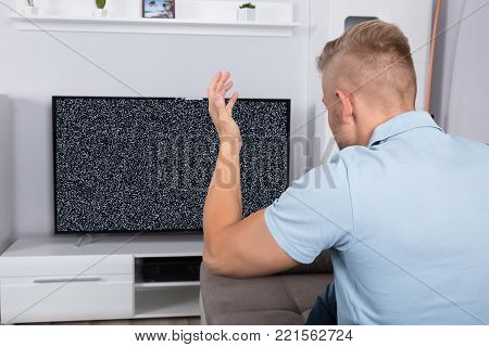 Frustrated Man Sitting On Sofa In Front Of Television With No Signal
