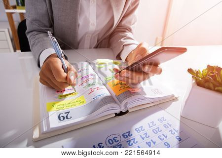 Midsection Of Person Hands With Mobile Phone And List Of Work In Diary On Desk
