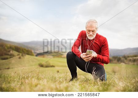 Active senior runner outside on green hills with smart phone and earphones, resting, listening music.