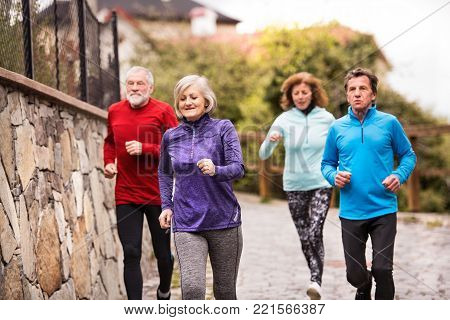 Group of active seniors running together outdoors in the old town of Banska Stiavnica in Slovakia.