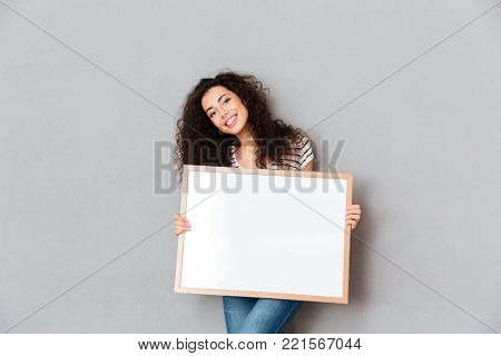 Caucasian woman with beautiful hair posing over grey wall holding piece of art in hands, expressing admiration about portrait copy space
